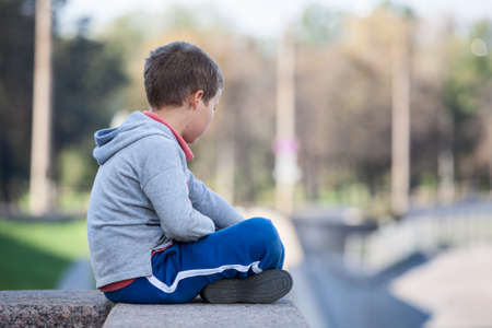 boys only: Side view of young boy sitting lotus position on granite curb
