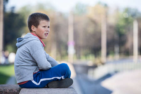 1 boy only: Thoughtful boy sitting on the edge of the granite plate, looks into the distance