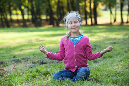 Young girl sitting in lotos pose with closed eyes on summer lawn photo