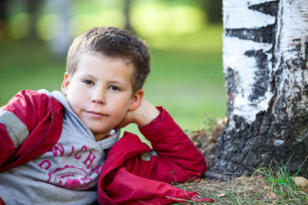 one boy only: Thoughtful boy in red jacket lying next to tree, copyspace, looking at camera