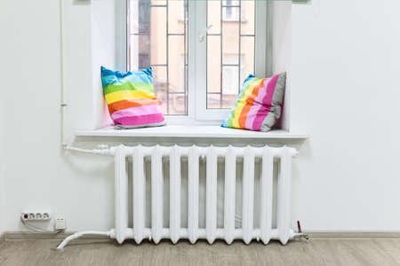 White iron radiator of central heating is under windowsill Standard-Bild