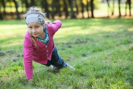 mignonne petite fille: Fille pr�scolaire faisant push-ups exercices avec une main sur l'herbe verte Banque d'images