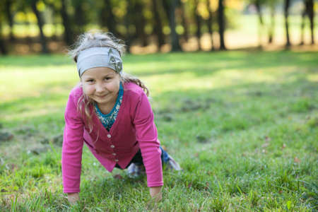 exercices: Preschool smiling girl making push-ups exercices on green grass in park