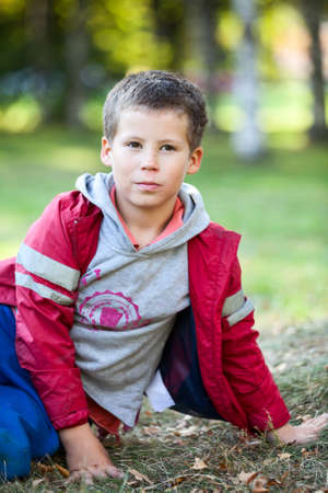��beautiful boy�: Beautiful boy in red jacket looking at camera outdoors