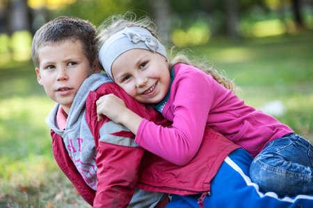 gemelos niÑo y niÑa: Feliz hermano y hermana jugando juntos en el parque de verano Foto de archivo
