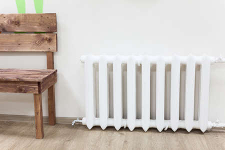 White iron radiator of central heating is near wooden bench in room Foto de archivo