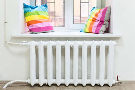 White radiator of central heating is in domestic room under window 免版税图像