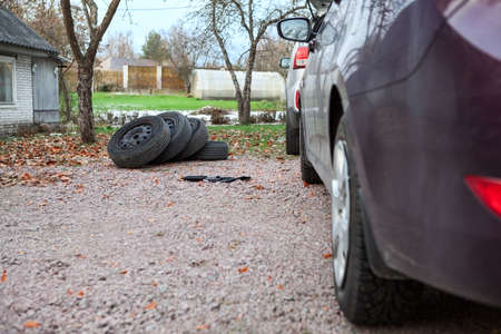 Four summer tire wheels laying in pile near car for replasement photo