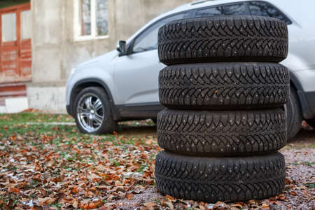 Four winter tyre wheels for changing are near car, copyspace photo
