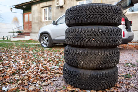 Four winter tire wheels ready for changing near car, copyspace photo