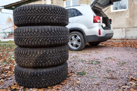 Set of winter wheels and tyres ready for changing are near car, copyspace photo