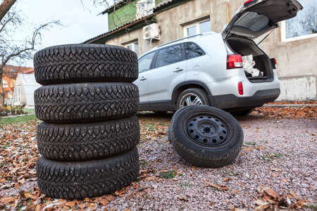 Two sets of winter wheels and tyres ready for replacement at car, copyspace photo
