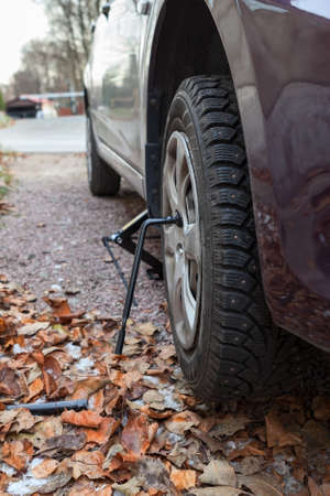 Studded tire wheel mounting on car with jack-screw at autumn photo
