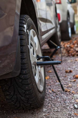 lifting jack: Winter studded tire wheel mounting on car with jack-screw at autumn