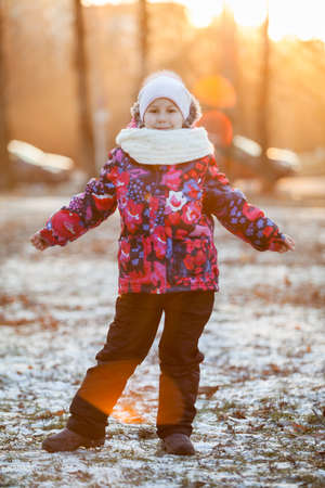 Six year old girl in warm clothes for a walk in the park, the rays of the setting sun photo