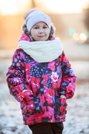 Portrait of pretty Caucasian girl standing in winter clothes with scarf and hat photo