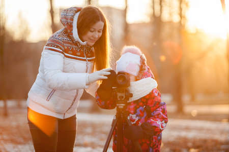 tripod mounted: Child under the supervision of mother pushing button of camera mounted on tripod