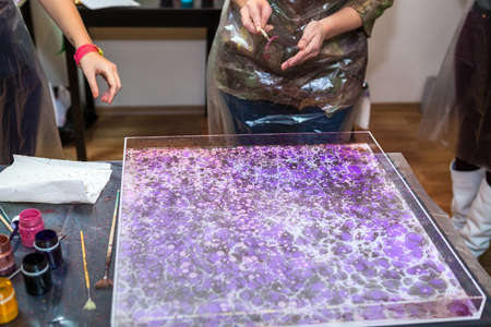 art lessons: People making ebru marbling, inks drawing on he water surface Stock Photo