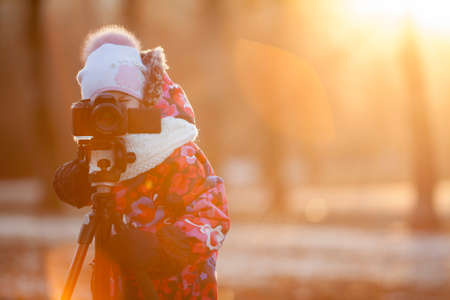 Pretty girl photographer taking pictures on camera using a tripod, sunset light, winter, copyspace photo