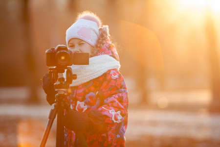 Young child photographer taking pictures on camera using a tripod, sunset light, copyspace photo