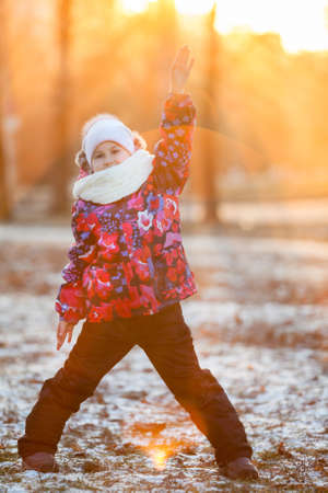 Child standing in the rays of the setting sun with a raised hand, winter photo