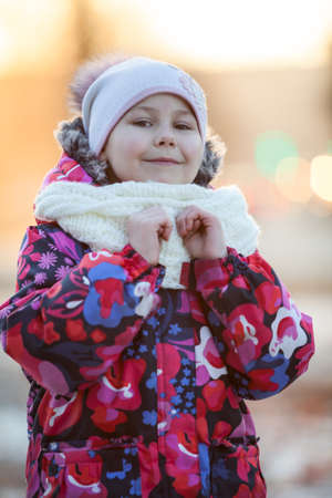 Pretty child in winter clothes standing outdoor. White scarf and hat photo