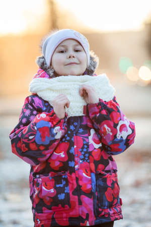 Pretty Caucasian girl in winter clothes standing outdoor. White scarf and hat photo