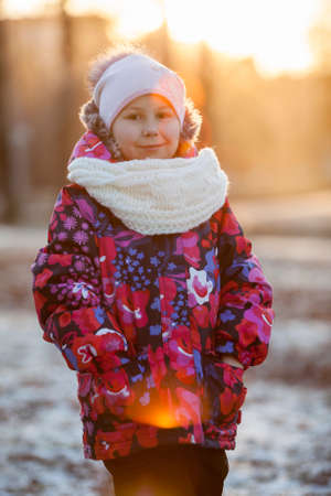 Portrait of young Caucasian girl standing at sunset light in winter clothes photo