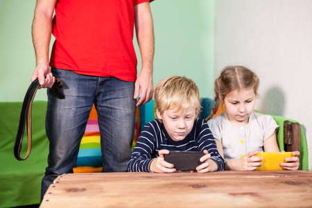 physical injury: Dad with a belt in his hand stands above children playing with mobile phones Stock Photo