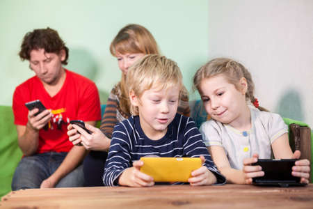strict: All family, kids and parents sitting with gadgets, playing the games in smartphones