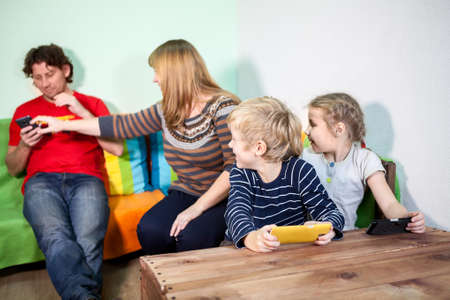 disobedience: Children are watching how their mother grabbing tablet pc from husband