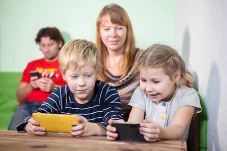 attention grabbing: Mom looking at children who play in the plates, the husband playing on the phone
