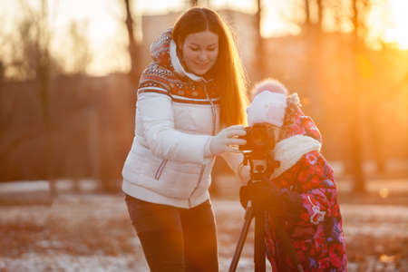 Mother and young daughter photographing with tripod together at a sunset light photo