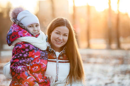 Portrait of Caucasian mother with a child, a frosty evening, sunshine, sunset photo