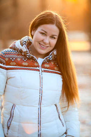 sun down: Portrait of attractive smiling woan in white down jacket in the sunlight