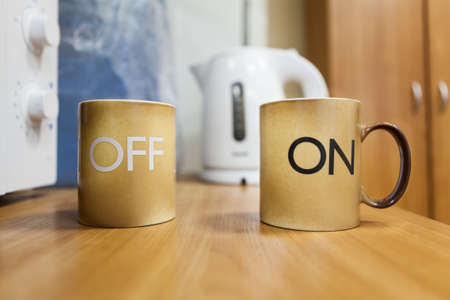 turning table: Two mugs with on off inscription standing on the table