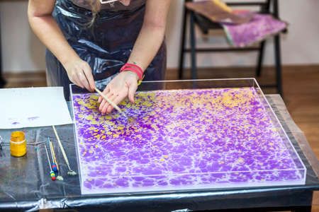 marbling: Painter hands splashing inks on water surface for marbling Stock Photo