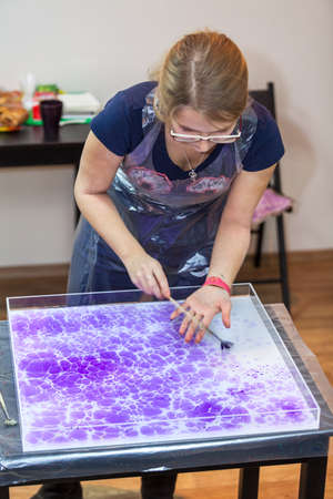 marbling: Young woman marbling on water surface with color inks