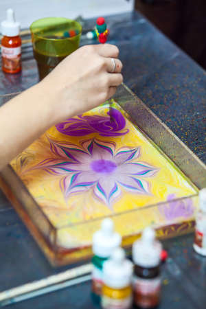 marbling: Painter working with basin for water surface marbling, drawing flower Stock Photo