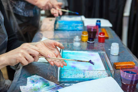 marbling: Hands of people which splashing paint over water surface, marbling Stock Photo