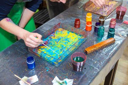 Schilder maken meesterwerk met inkt te laten vallen op het wateroppervlak