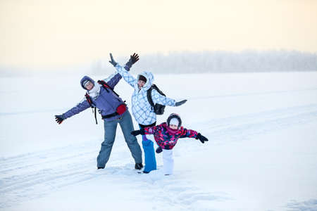 Happy laughing mature woman, young woman and girl posing on frozen winter lake photo