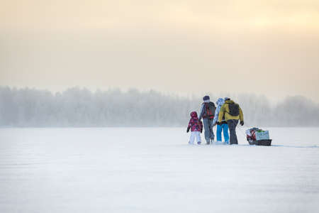 People travel through the blizzard on frozen lake at winter photo