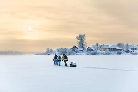 wintery day: People traveling over frozen lake at beauty sunset, cold weather