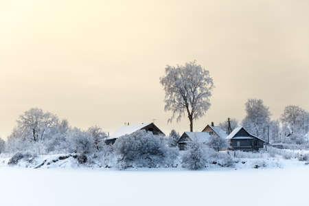 lake house: Lake shore with timber houses at winter season with sunset sky Stock Photo
