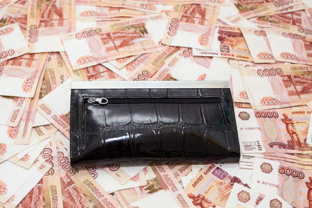 thousandth: Black purse on scattered five thousandth banknotes of rubles