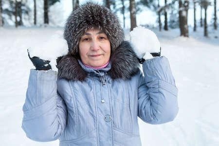 ancianos caminando: Superior nieve levantamiento mujer en las manos, la temporada de invierno Foto de archivo