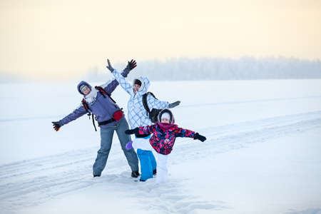 wintery day: Caucasian family from three women standing with raising hands on frozen lake, winter hiking