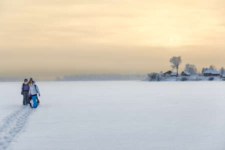 winter vacation: Family standing on ice of frozen lake while hiking to home, copyspace