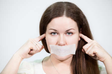 Caucasian young woman with glued tape on her mouth and closed ears, grey background photo